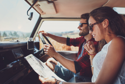 Generation Z couple plan their next stop on a road-trip, whilst driving through the desert